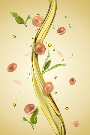 Argan fruits and seeds with a splash of oil an green background