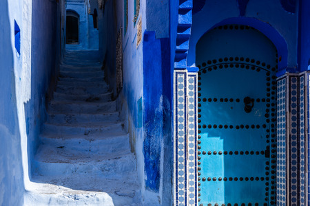 Street and door of the old Medina of Chefchaouen, the Moroccan blue city,