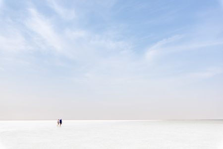 ASSALE LAKE, ETHIOPIA -- AUGUST 17, 2018: unidentified couple walks on the salty surface of lake Assale. This  lake is one of the saltiest of the world. Editorial