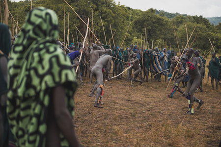 KIBISH, ETHIOPIA - AUGUST 22, 2018: unidentified men from Surmi tribe, in a village near Kibish fight in the Donga, a ritual stick fighting, to prove their strenght