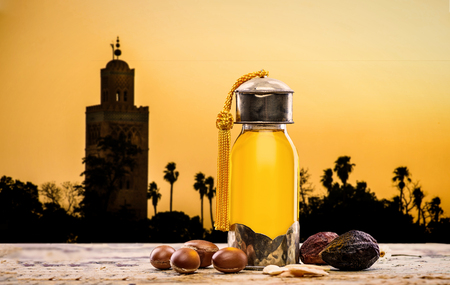 Bottle of argan oil and fruits for skin care with moroccan landscape on the background Stock Photo