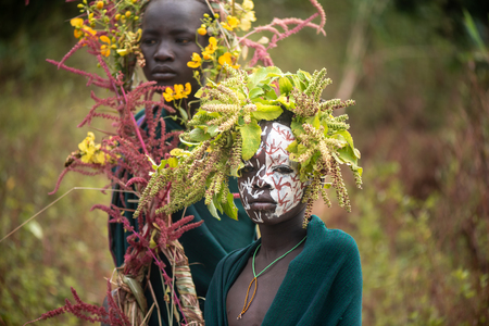 KIBISH, ETHIOPIA - AUGUST 22, 2018: unidentified boy from Surmi tribe, with painted face and natural decorations of leave. Surmi are also called Suri or Surma