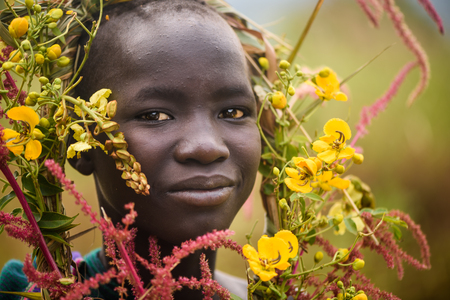 KIBISH, ETHIOPIA - AUGUST 22, 2018: unidentified woman from Surmi tribe, with  natural decorations of leave and flowers in a wreath. Surmi are also called Suri or Surma