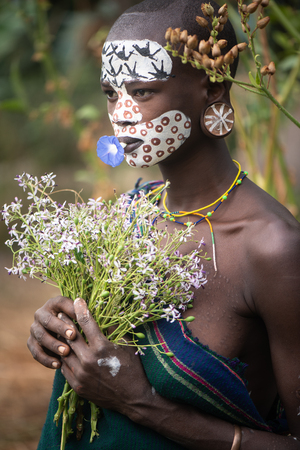 KIBISH, ETHIOPIA - AUGUST 22, 2018: unidentified woman from Surmi tribe, with flower decorations. Surmi are also called Suri or Surma and live in villages in the south wester part of Ethiopia