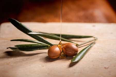 Argan oil, used for cosmetics, puring over two argan seeds on a stone table.