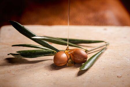 Olio di argan, utilizzato per i cosmetici, purificando su due semi di argan su un tavolo di pietra. Archivio Fotografico