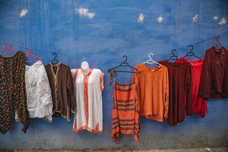 Bunte Kleider hängen an einer Wand in einer Straße von Chefchaouen Standard-Bild
