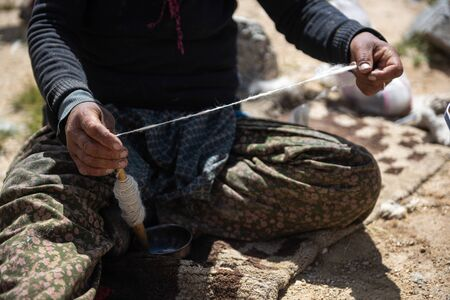 Hands of a woman spinning wool fibres