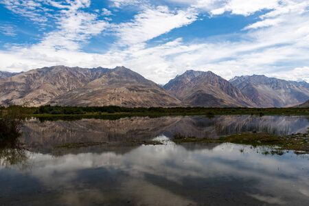 High mountains in the Nubra Valley, India, reflected in a river Stock Photo