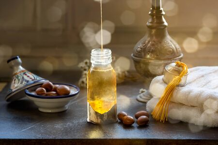 Glass bottle of Argan oil on a table with argan fruits