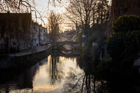 water canals of Bruges, Belgium, in a winter sunny day at sunset