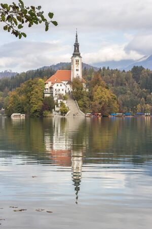 Lake Bled Slovenia. Beautiful mountain lake with small church. The Slovenian lake and island with the church of the Assumption of Mary and the reflection in calm waters. Imagens