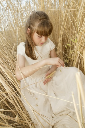girl wearing first communion dress among the spikes photo