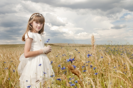 innocent: girl wearing first communion dress among the flowers and spikes Stock Photo