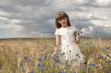 girl wearing first communion dress among the flowers and spikes photo