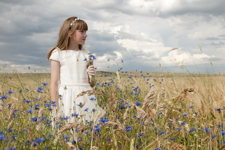 among: girl wearing first communion dress among the flowers and spikes Stock Photo
