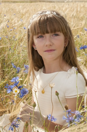 girl wearing first communion dress among the flowers and spikes Standard-Bild