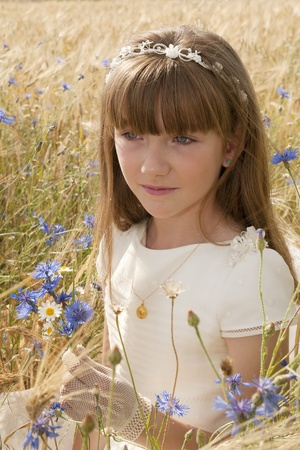 girl wearing first communion dress among the flowers and spikes Stock Photo - 10082253