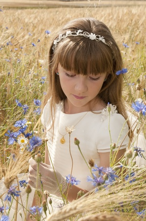 girl wearing first communion dress among the flowers and spikes Stock Photo - 10082261