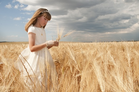 girl wearing first communion dress among the spikes Standard-Bild