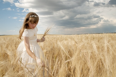 girl wearing first communion dress among the spikes Stock Photo