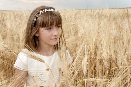 chica con vestido de primera comunión entre la cebada Stock Photo - 10082255