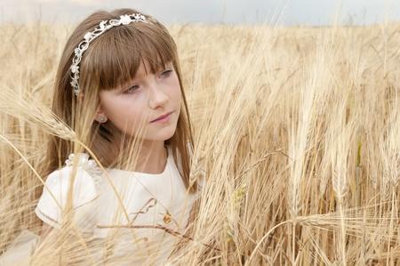 chica: chica con vestido de primera comunión entre la cebada