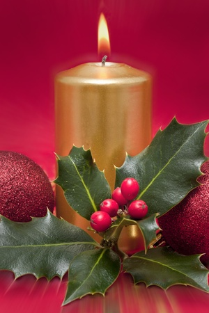 holding a christmas ornament: Christmas Cards with candles and holly plant Stock Photo