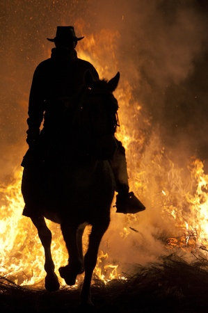 rider jumps the fire with his horse