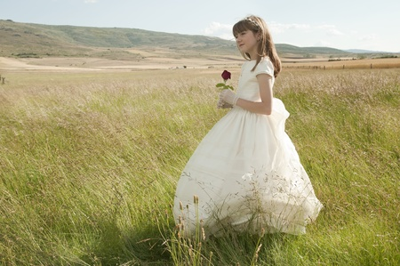 christian confirmation: girl wearing first communion dress in the meadow