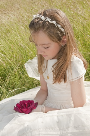 girl wearing first communion dress in the meadow photo