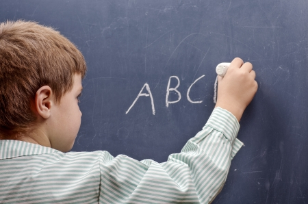 boy writing alphabet on chalkboard Stock Photo