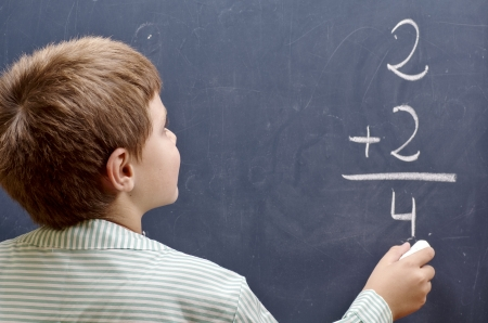 child writing sum on blackboard photo