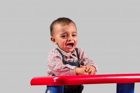 child crying: Imagen de un niño que llora en el vivero en gris