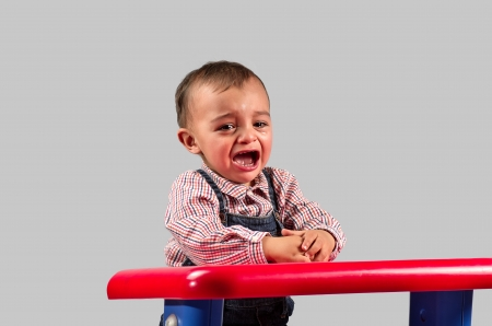 crying child: Picture of a child crying in the nursery in gray Stock Photo
