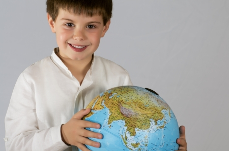 photo of a child posing with a globe