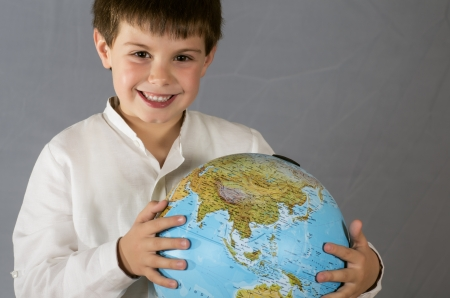 a child posing with a globe on gray background Stock Photo