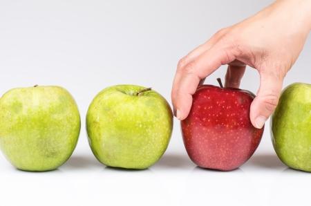 fotografía de una mano recogiendo manzanas para elegir