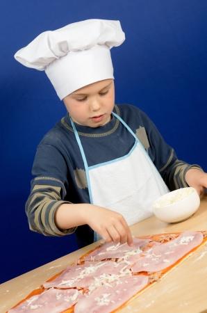 photograph of a child preparing a pizza photo