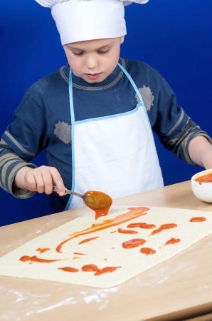 a child preparing a pizza photo