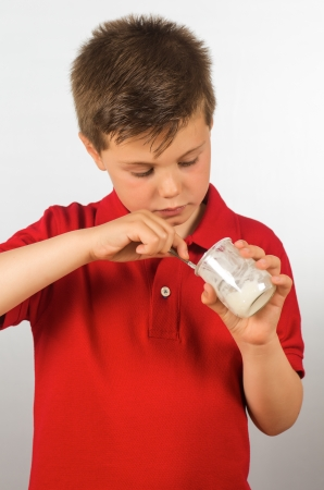 photograph of a child eating yogurt over white background photo