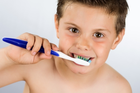 photograph of portrait of a boy brushing his teeth photo