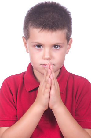 praying child with red sweater on a white background photo