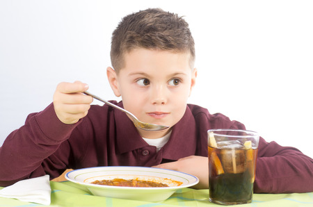 Studio photograph of a child eating a delicious lentil stew with potatoes and sausage photo