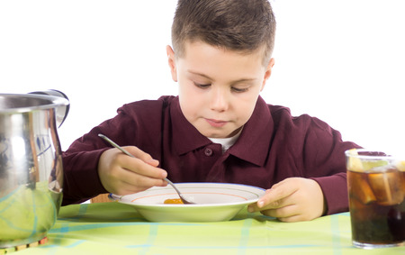 Studio photograph of a child eating a delicious lentil stew with potatoes and sausage