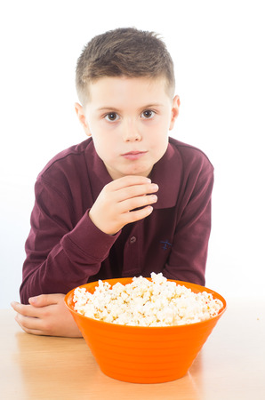 photographic portrait of a boy eating some delicious popcorn