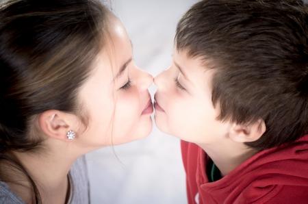 photographic portrait of two innocent children kissing