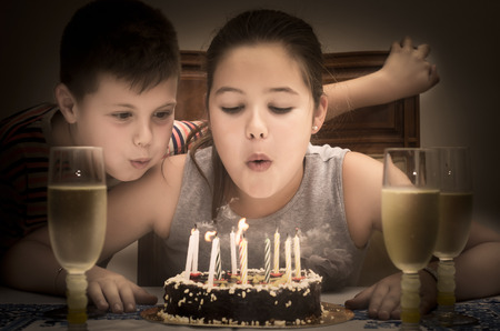 photograph of two children blowing out candles on her birthday cake photo