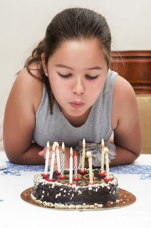 childs birthday party: photograph of two children blowing out candles on her birthday cake