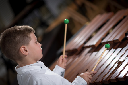 portrait of a young man learning to play the xylophone Stock Photo
